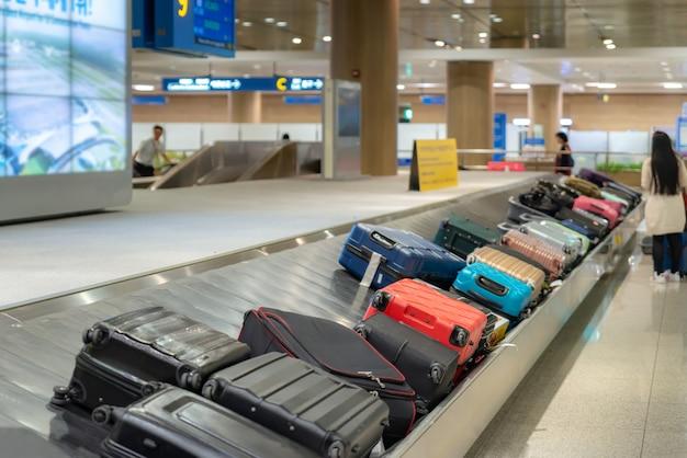 Valise ou bagages avec tapis roulant à l'aéroport.