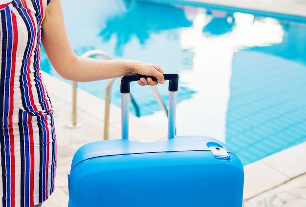 Valise bleue, chapeau et lunettes de soleil près de la piscine