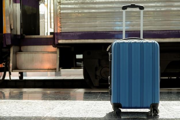 La valise bleue est placée sur le quai du train.