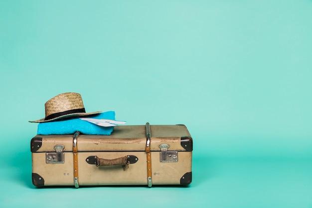 Valise brune avec des papiers de chapeau et un chiffon dessus