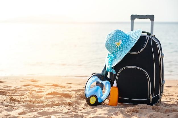 Valise et chapeau, crème solaire avec un masque.