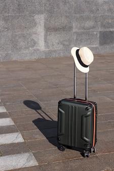 Valise avec un chapeau de paille sur fond gris