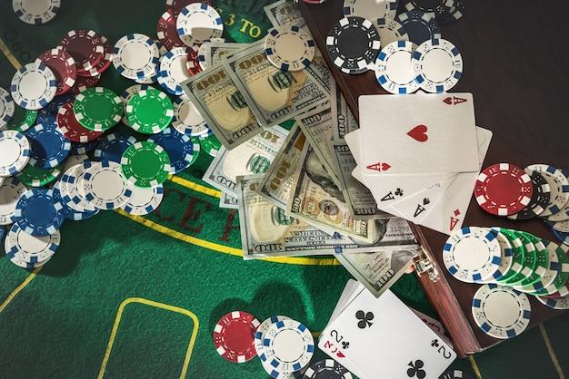 Valise avec des dollars, une carte à jouer, des jetons de poker sur la table de poker verte.