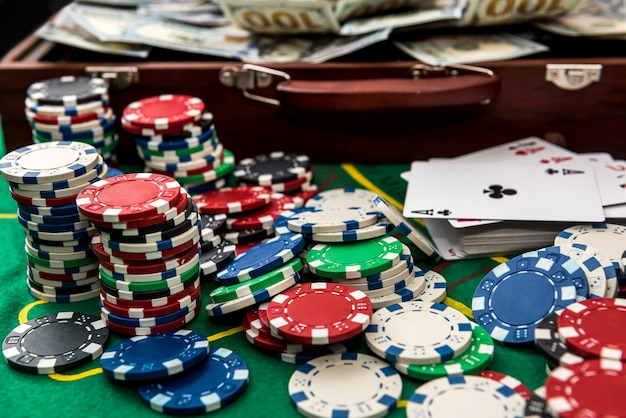 Valise avec dollars, carte à jouer, jetons de poker sur la table de poker verte.