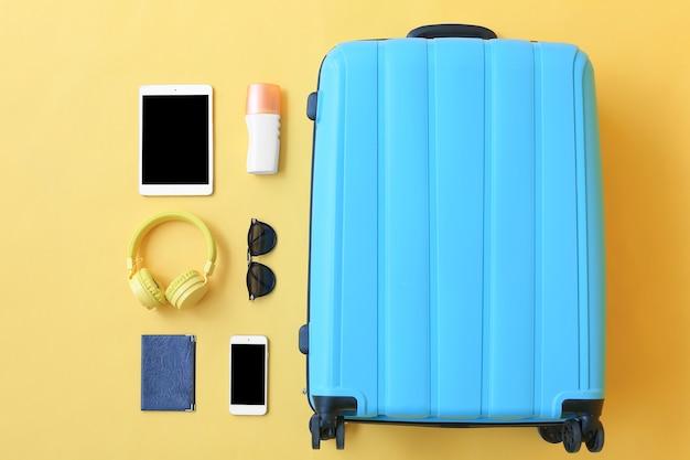 Valise emballée avec accessoires et appareils de plage sur orange, vue du dessus