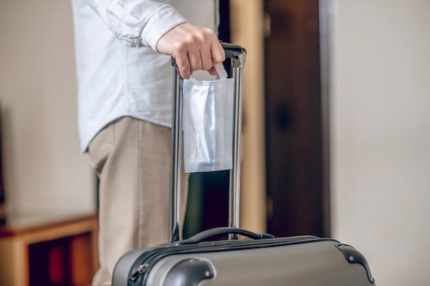 Avec valise. gros plan photo d'une main d'homme tenant une valise