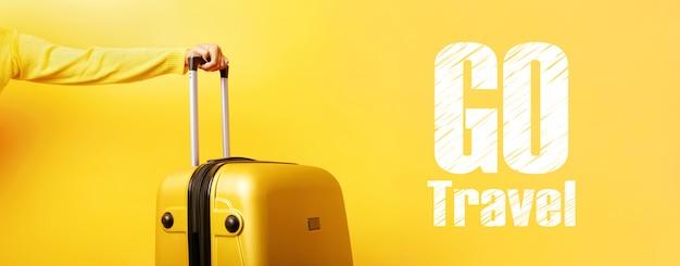 Valise jaune à la main et inscription aller voyager sur mur jaune, concept de voyage,