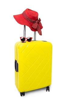 Valise jaune de voyage avec lunettes de soleil et chapeau rouge isolé sur fond blanc.