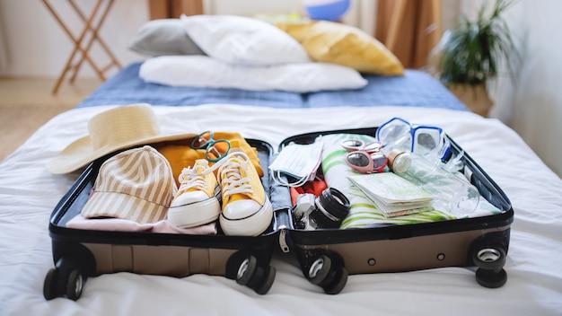Une valise ouverte emballée pour des vacances au lit à la maison, concept de coronavirus.