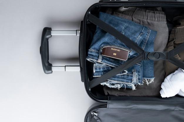 Valise ouverte emballée pour voyager avec un passeport thaïlandais sur fond gris