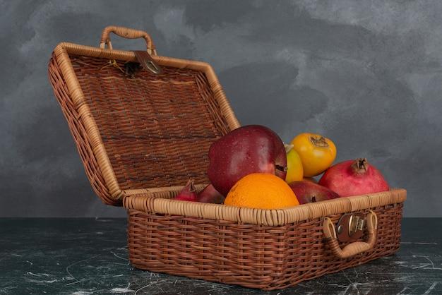 Valise ouverte pleine de fruits sur un mur de marbre.