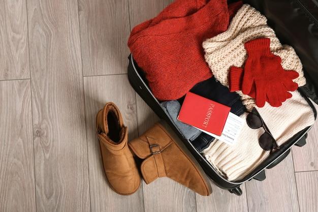 Valise ouverte avec des vêtements chauds et des documents sur un plancher en bois. concept de vacances d'hiver