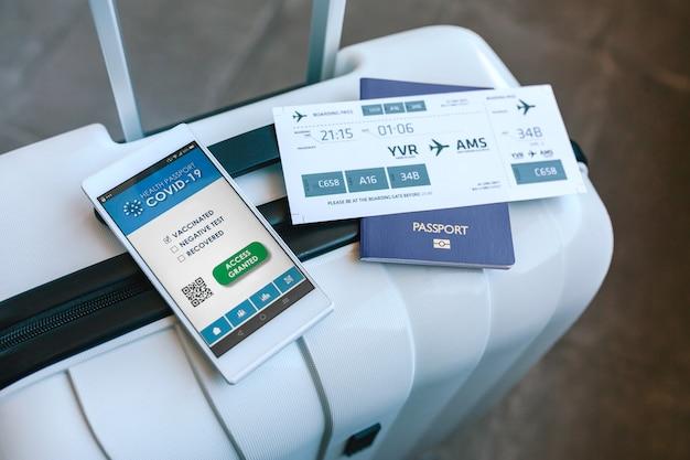 Valise avec passeport, carte d'embarquement et passeport covid sur le mobile
