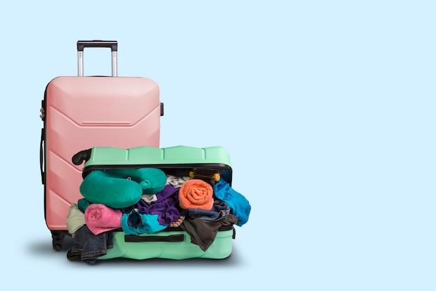 Valise en plastique ouverte avec des roues, bondée de choses et une petite valise debout à côté d'un fond bleu. concept de voyage, voyage de vacances, visite à des proches