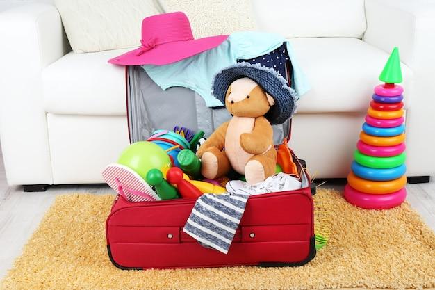 Valise remplie de vêtements et de jouets pour enfants sur un tapis en fourrure et un canapé blanc
