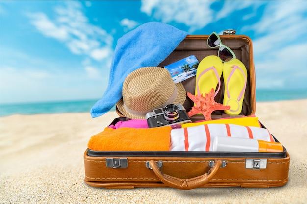 Valise rétro avec des objets de voyage sur fond de mer