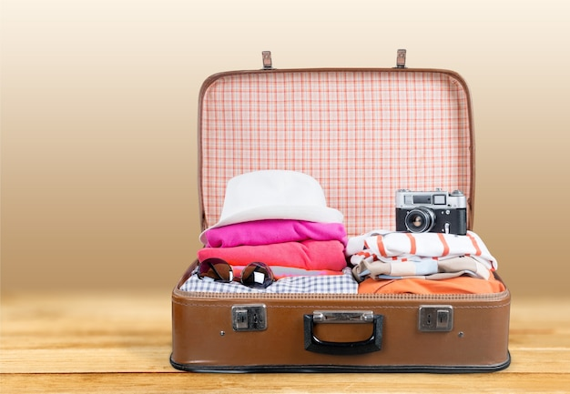 Valise rétro avec des objets de voyage sur fond