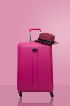 Valise rose avec un chapeau sur fond rose pastel. concept de voyage.