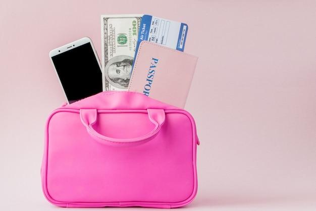 Valise rose voyageur et document de passeport, sac à main sur fond rose, concept de voyage et de voyage.
