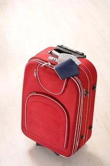 Valise rouge, passeports et argent sur un plancher en bois dans une salle vide