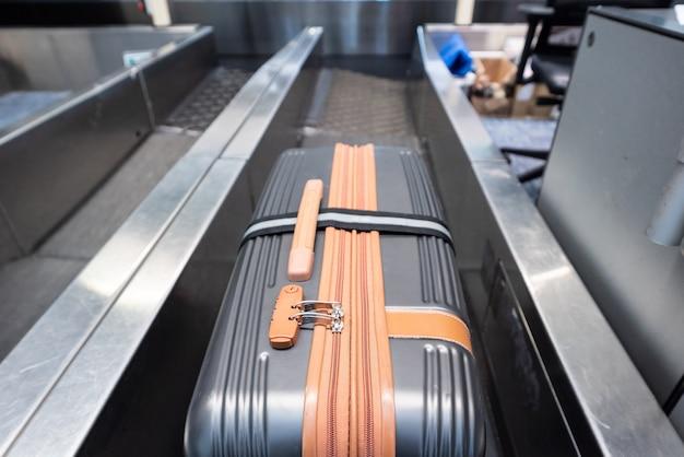 Valise sur le système de convoyeur à bagages à l'enregistrement dans l'aéroport