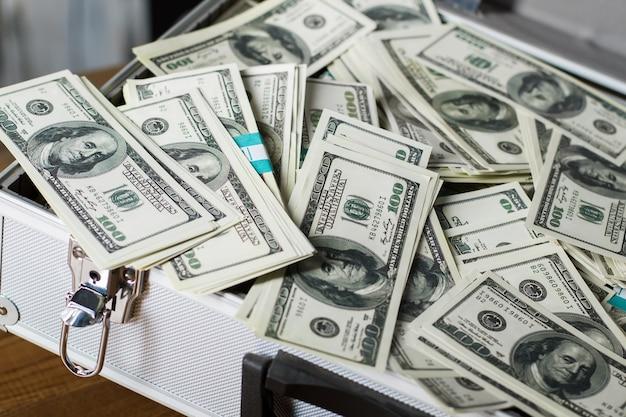 Valise avec tas de dollars. boîtier en argent ouvert avec de l'argent. mieux vaut avoir un compte bancaire. une partie du budget de la ville.