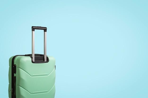 Valise vert clair sur roues sur fond bleu clair. concept de voyage, voyage de vacances, visite à des proches