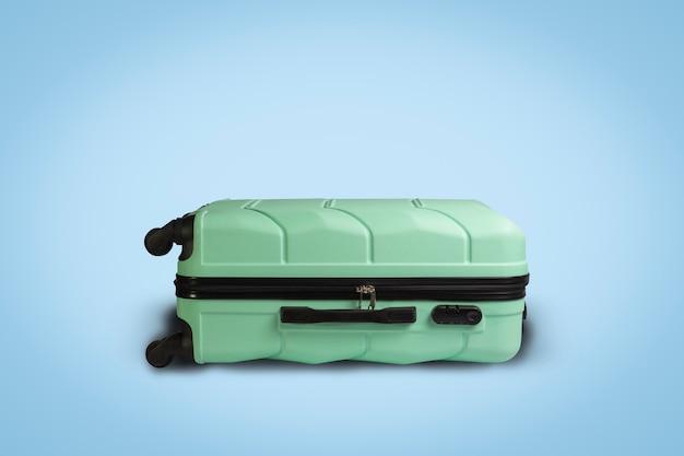 Valise vert clair sur roues sur fond bleu. concept de voyage, voyage de vacances, visite à des proches