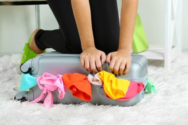 Valise avec des vêtements sur un tapis dans la chambre
