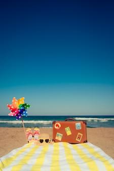 Valise vintage et articles de plage contre la mer et le ciel bleus