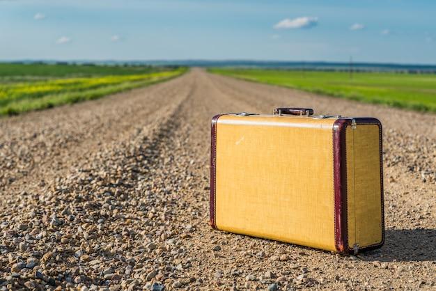 Valise vintage au milieu d'une route de campagne dans les prairies