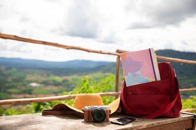 Valise vintage, chapeau hipster, appareil photo et passeport sur une terrasse en bois.