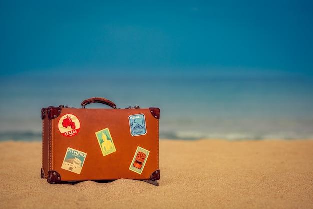 Valise vintage sur la plage de sable contre le bleu de la mer et du ciel concept de vacances et de voyage d'été