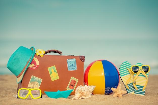 Valise vintage et tongs sur la plage de sable contre la mer et le ciel bleus