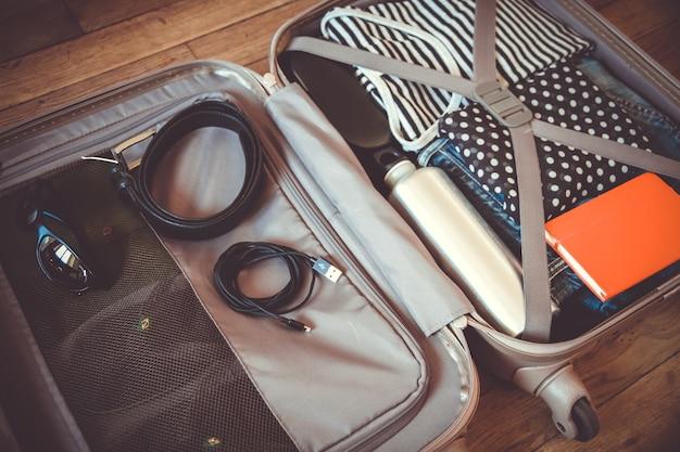 Valise de voyage ouverte pleine de vêtements isolés sur fond de bois