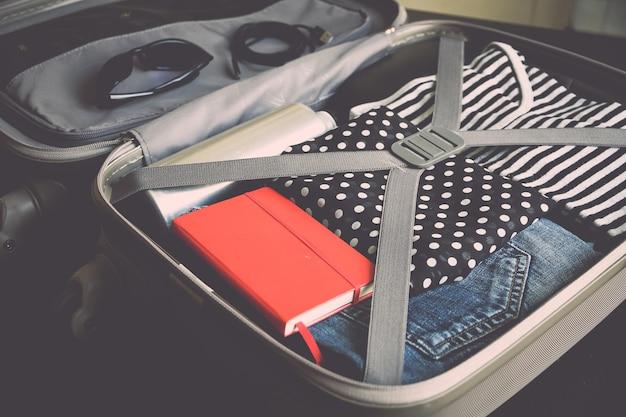 Valise de voyage ouverte pleine de vêtements isolés sur une surface noire