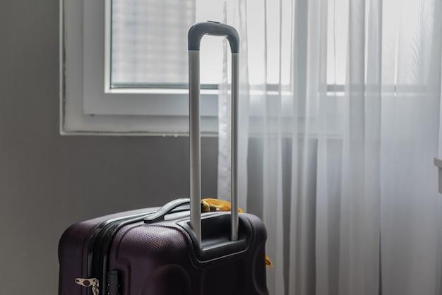 Valise de voyage sur le sol avec rideau en arrière-plan.