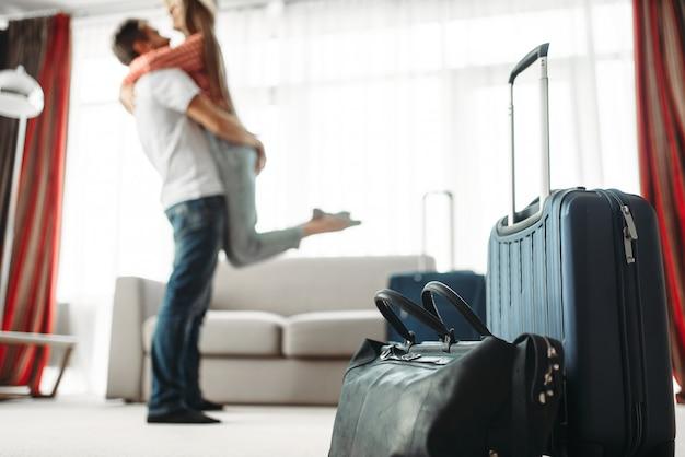 Valises préparées pour les vacances, couple heureux câlins