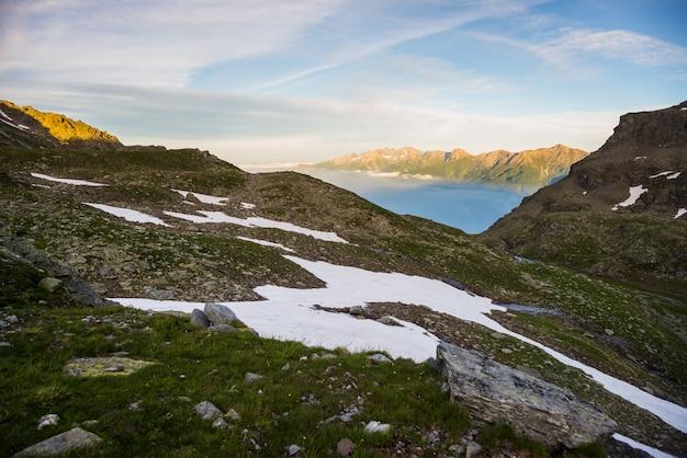 Vallée alpine rougeoyante au coucher du soleil d'en haut