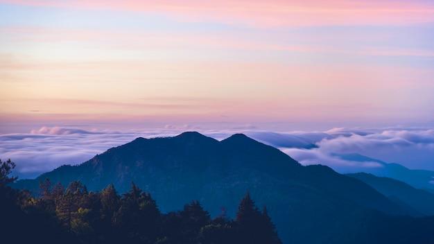 Vallée de brouillard de montagne pendant le lever du soleil.le mur de la nature avec du brouillard sur la montagne, par temps pluvieux dans la campagne