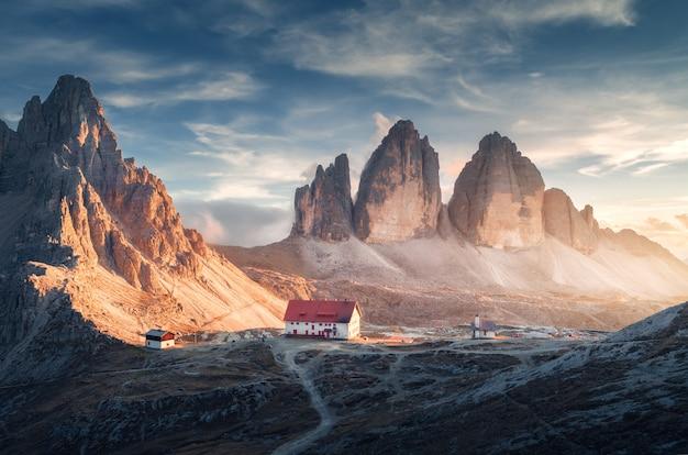Vallée de montagne avec belle maison et église au coucher du soleil en automne. paysage avec bâtiments, hautes roches, sentier, ciel bleu et soleil.