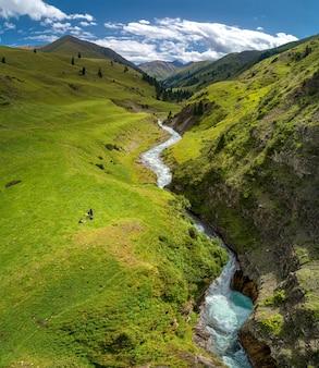 Vallée de montagne avec rivière et cascade, vue plongeante