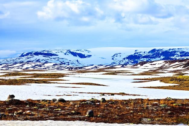 Vallée de neige, les montagnes au loin et le ciel