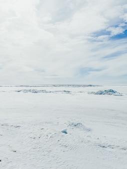 Vallée recouverte de neige sur une froide journée d'hiver sous le ciel nuageux