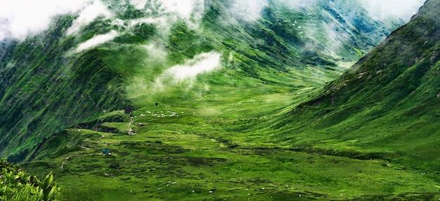 Vallée verte avec des nuages et des tentes de camping bzerpinskiy karniz dans les montagnes de krasnaya polyana