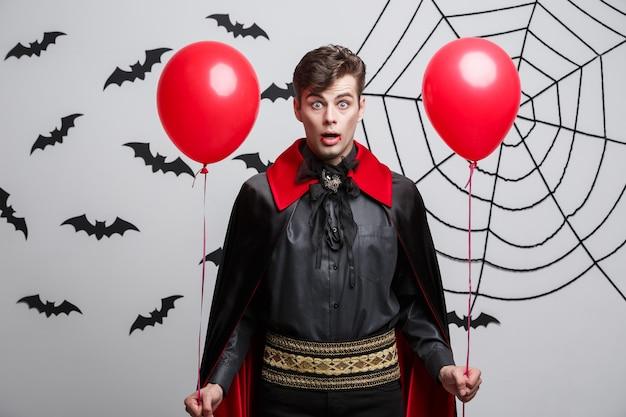 Vampire halloween concept - portrait de beau caucasien en costume d'halloween vampire avec ballon coloré.