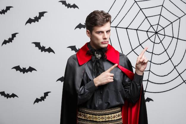 Vampire halloween concept - portrait de beau caucasien en costume d'halloween vampire pointant sur le côté.