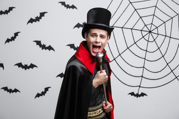 Vampire halloween concept - portrait de beau vampire caucasien en costume d'halloween noir et rouge chantant avec le personnel.