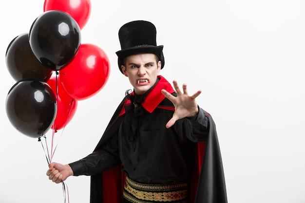 Vampire halloween concept - portrait complet de beau vampire caucasien en costume d'halloween noir et rouge.