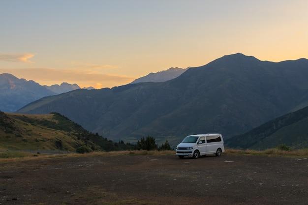 Van blanc garé dans un parking entre les montagnes